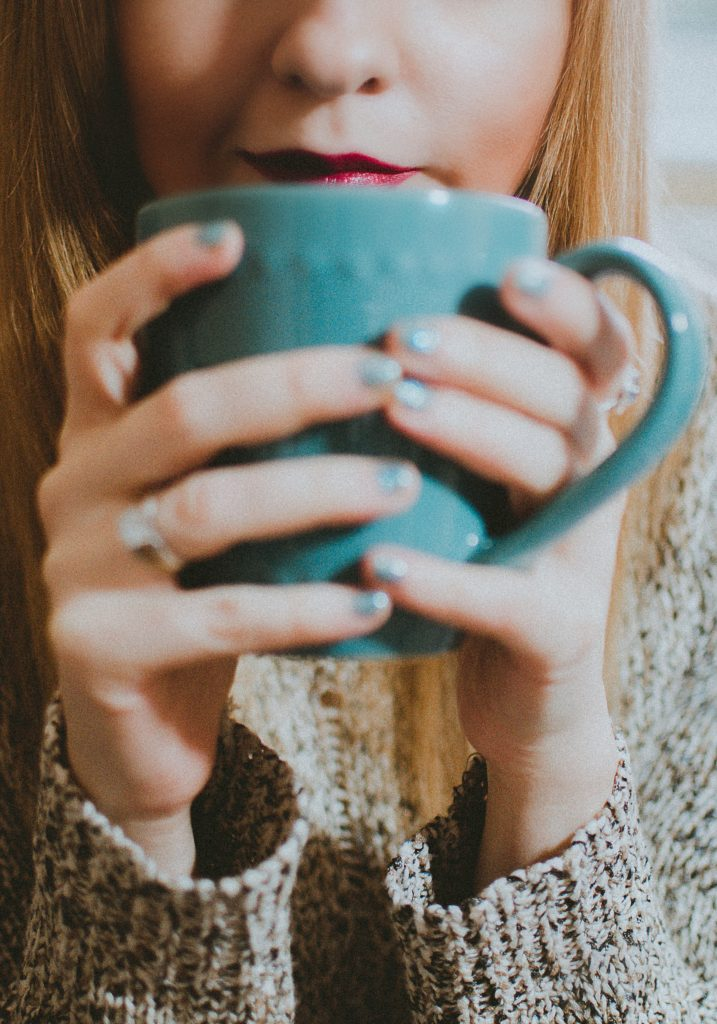 Woman holding a blue tea cup close to her face