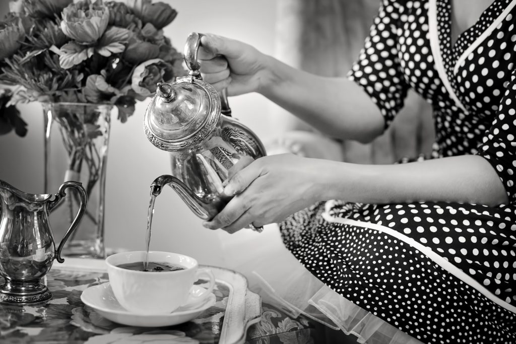 Lady pouring English breakfast tea into a cup from a teapot