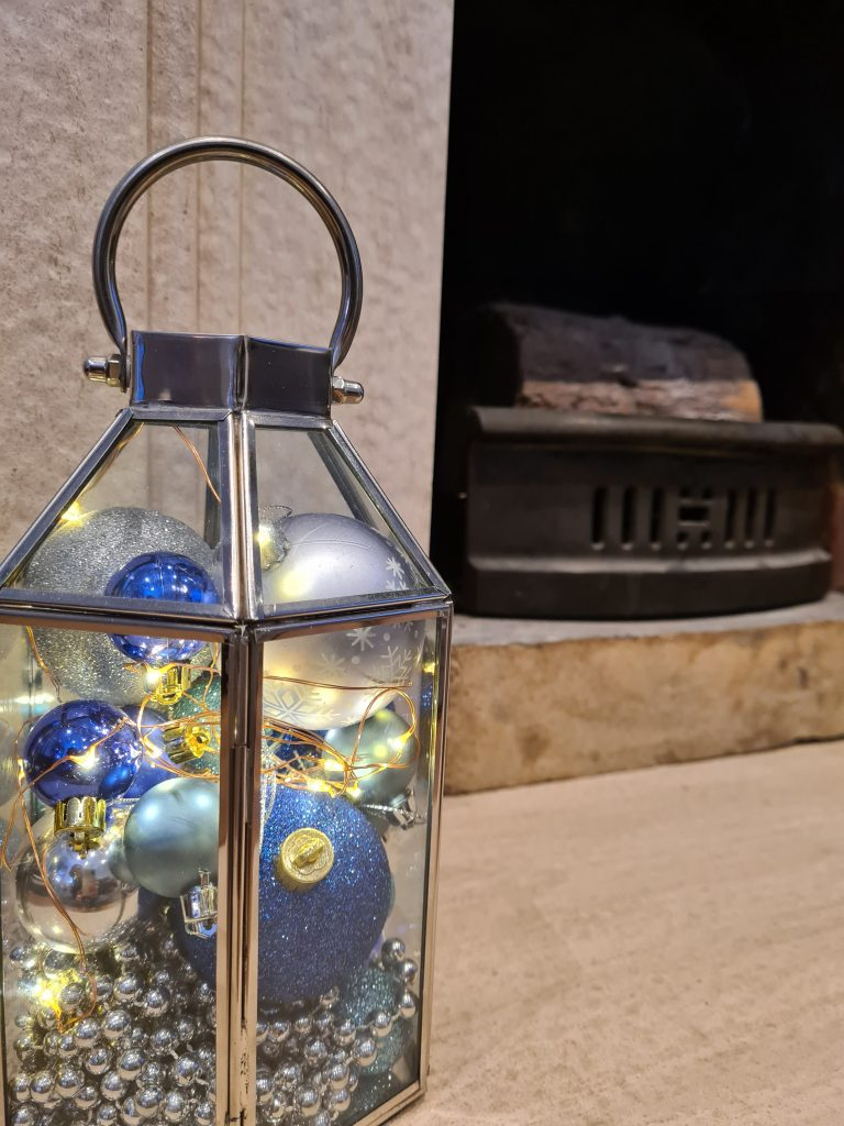 Home made Christmas decoration - blue and silver baubles with battery operated lights in a silver lantern