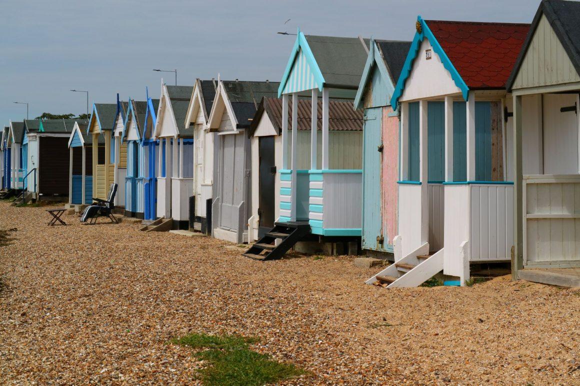 Colourful beach huts lined on a stony beach