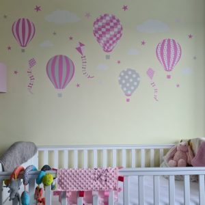 Pink hot air balloon wall stickers above a cot