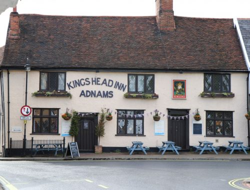 Cream walled pub with blue benches outside