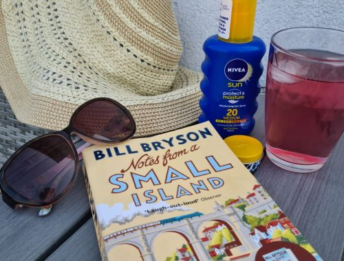 Notes on a Small Island paperback book on table with summer hat, sunglasses, juice, and suncream