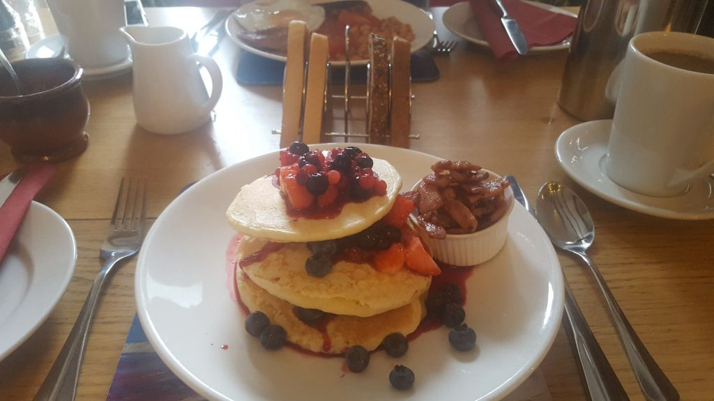 Breakfast pancakes with fruit, maple syrup, and bacon