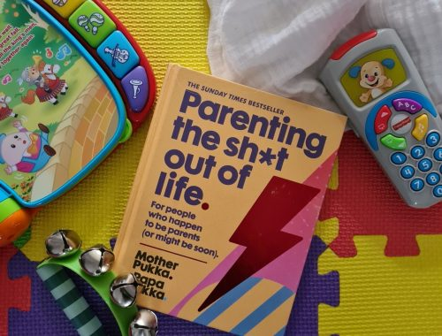 Hardback Parenting the shit out of life book on children's play mats surrounded by toys