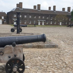 Cannon in foreground of cobblestone courtyard. A row of brown brick terrace houses are in the distance.