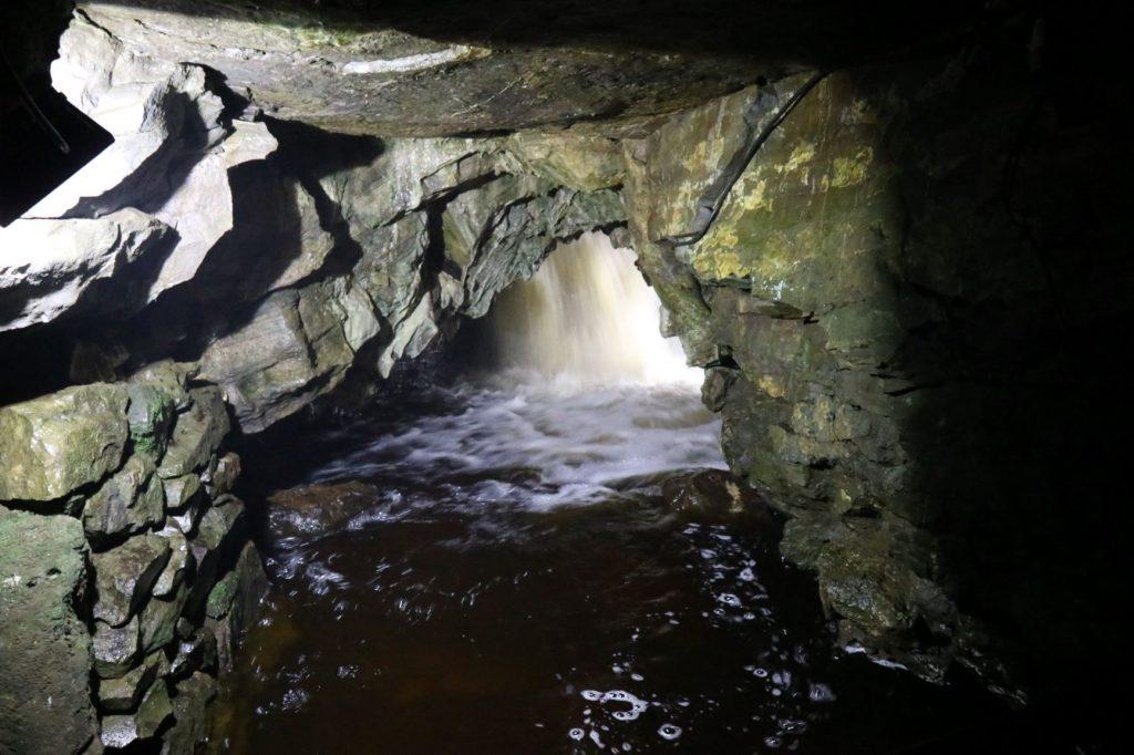 Waterfall behind an underground arch
