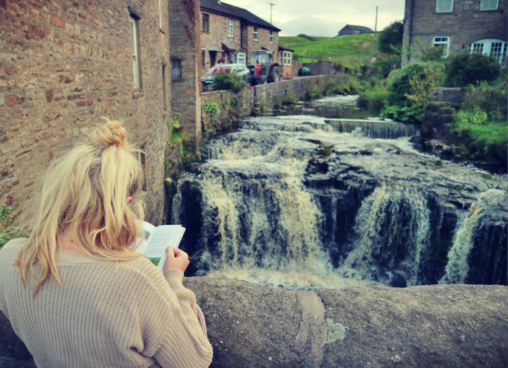 Woman looking at walking guide in front of Hawes waterfall