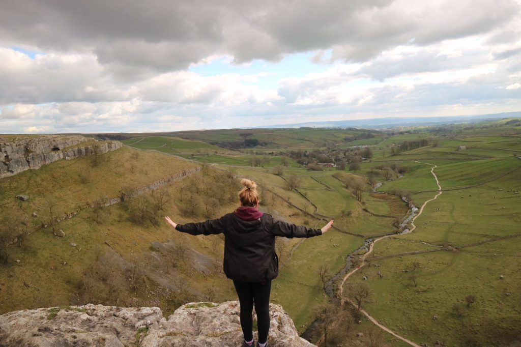 Woman with open arms on the edge of Malham Cove, looking over the valley