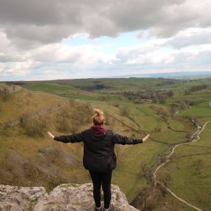 Woman on edge of Malham Cove, looking over valley
