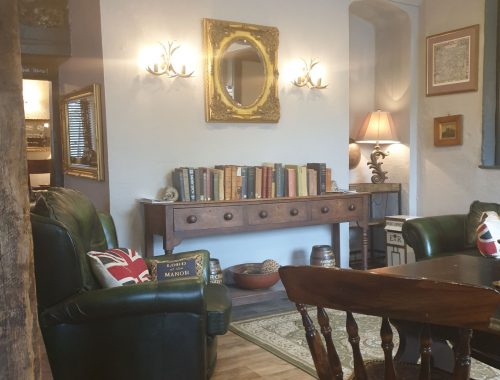 Green leather seating, and dark wood furniture in sitting room style pub