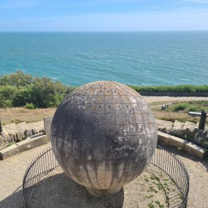 Large stone globe in circular platform in front of sea