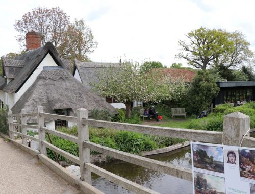 Thatched roof cottage next to a wooden bridge and river