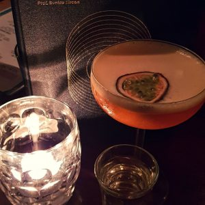 Pornstar martini beside a candle and menu