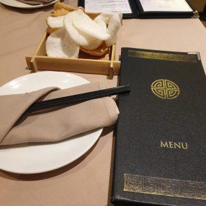 Menu, plate with chopsticks, and prawn crackers