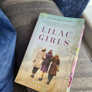 Front cover of Lilac Girls paperback - three women in 1940s clothing shown from behind in centre of book cover, and title printed in purple font