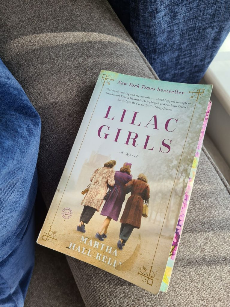 Paperback copy of Lilac Girls resting on an armchair