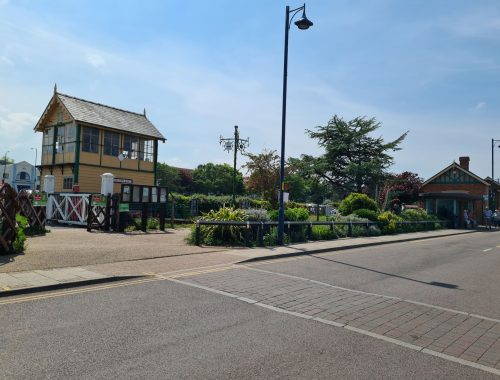 Yellow signal box, brick station building, and summer hedges of a train station on opposite side of the road