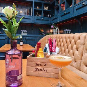 Pornstar martini, decorative gin bottle, and cutlery box on table