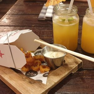 Calamari served in Chinese take out style box with two yellow cocktails served in jam jars
