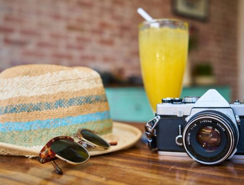 Hat, sunglasses, cocktail and camera on a table