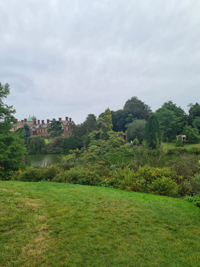 Sandringham House behind plant life and a small lake